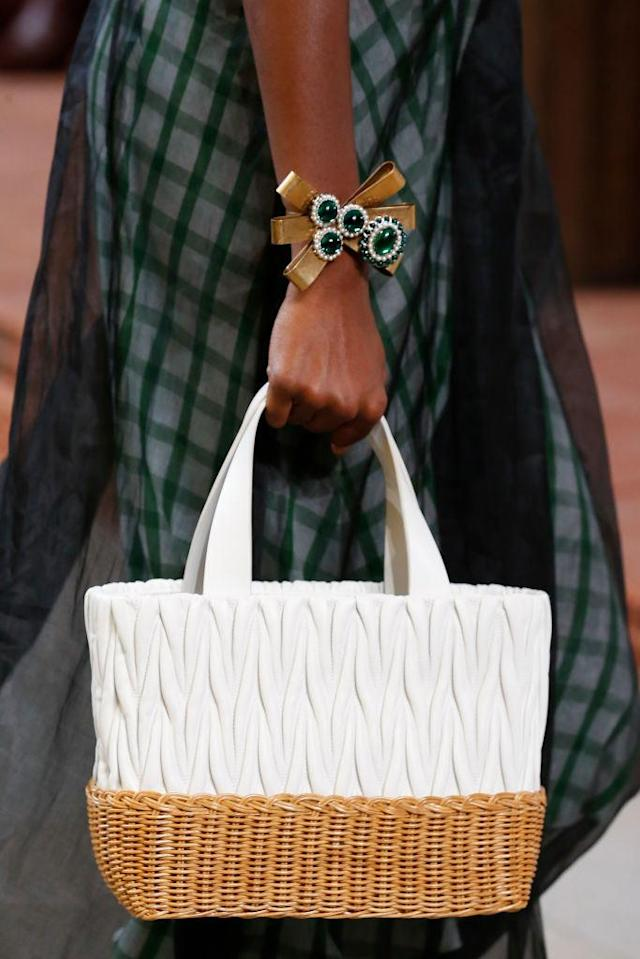 <p>A model carries a white basket tote bag during the Miu Miu spring/summer 2018 show in Paris. (Photo: Getty Images) </p>