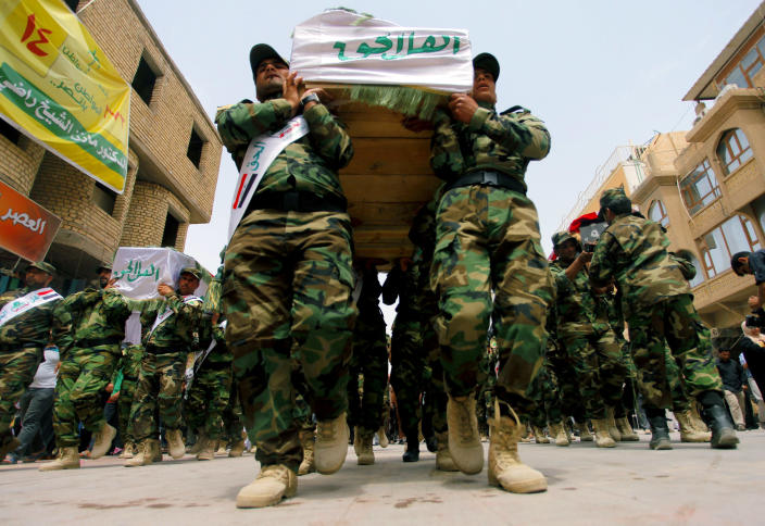 FILE - In this file photo taken Saturday, April 26, 2014, mourners carry the flag-draped coffins of five militia members of a Shiite group, Asaib Ahl al-Haq, or League of the Righteous, during their funeral procession in the Shiite holy city of Najaf, 100 miles (160 kilometers) south of Baghdad, Iraq. As parliamentary elections are held Wednesday, April 30, more than two years after the withdrawal of U.S. troops, Baghdad is once again a city gripped by fear and scarred by violence. (AP Photo/Jaber al-Helo, File)