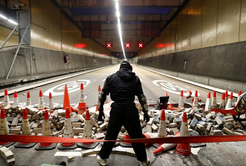 FILE PHOTO: An anti-government protester stands at a blocked outlet of the Cross Harbour Tunnel near the Polytechnic University in Hong Kong