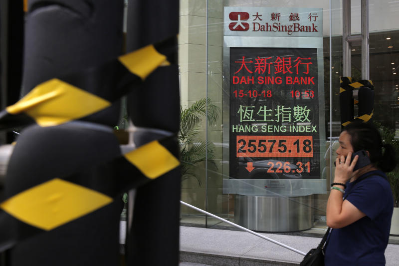 A woman walks past an electronic board showing Hong Kong share index outside a bank In Hong Kong, Monday, Oct. 15, 2018. Asian stocks slipped Monday, as investor worries continued about global trade tensions and prospects for economic growth. (AP Photo/Kin Cheung)