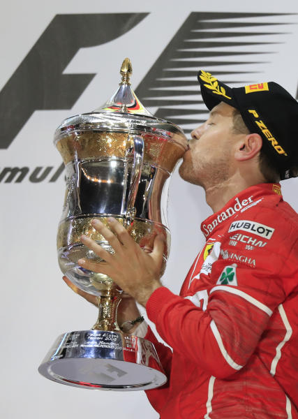 Ferrari driver Sebastian Vettel of Germany kisses his trophy after winning the Bahrain Formula One Grand Prix, at the Formula One Bahrain International Circuit in Sakhir, Bahrain, Sunday, April 16, 2017. (AP Photo/Hassan Ammar)