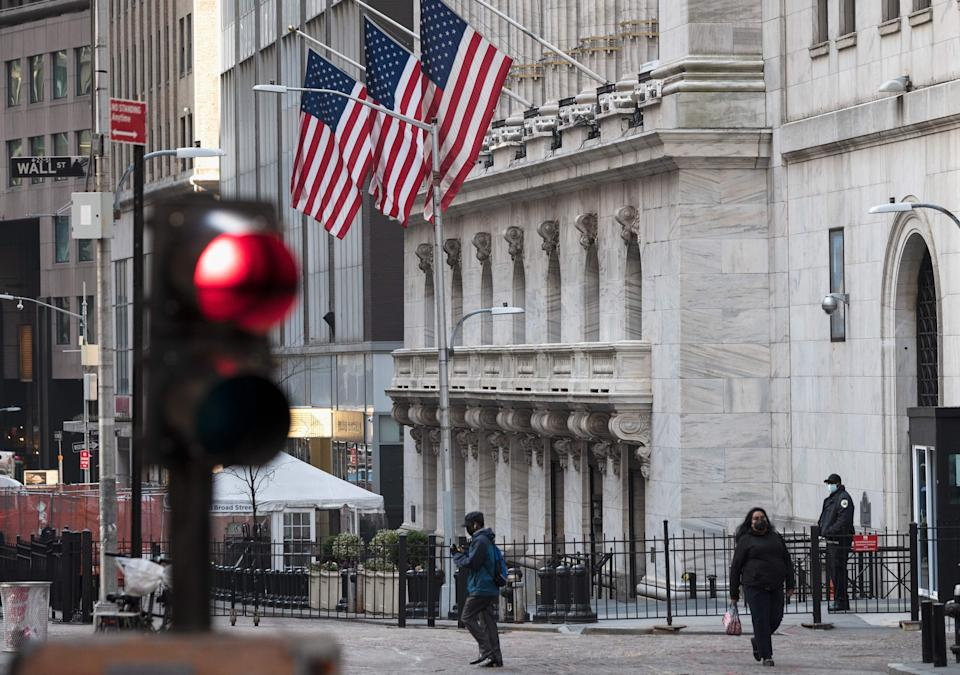 People walk past the New York Stock Exchange (NYSE) at Wall Street on March 23, 2021 in New York City. - Wall Street stocks were under pressure early ahead of congressional testimony from Federal Reserve Chief Jerome Powell as US Treasury bond yields continued to retreat. (Photo by Angela Weiss / AFP) (Photo by ANGELA WEISS/AFP via Getty Images)