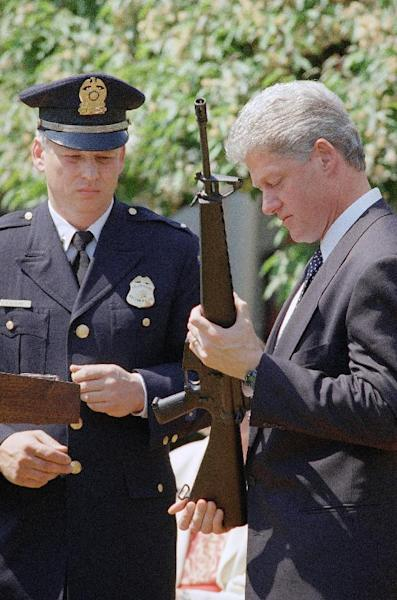 FILE - In this April 25, 1994 file photo, President Bill Clinton holds a Colt AR-15 rifle during a ceremony in the Rose Garden of the White House in Washington, where he launched efforts to pass the assault weapons ban. Dayton, Ohio Police Lt. Randy Bean, whose fellow officer Steve Whalen was gunned down with an AR-15 in 1991, looks on at left. (AP Photo/Dennis Cook)