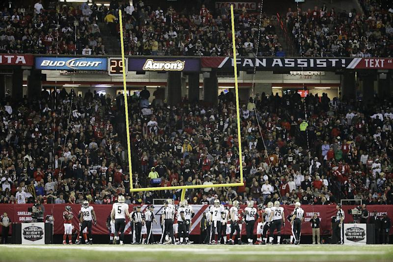 In this Nov. 21, 2013, file photo, the goal post leans after New Orleans Saints tight end Jimmy Graham dunked the ball and hung from the post against the Atlanta Falcons during the first half of an NFL football game in Atlanta. Players no longer will be allowed to dunk the football over the crossbar of the goalposts in celebration. Director of officiating Dean Blandino said the NFL is making a clarification of the rules for mutual respect and sportsmanship