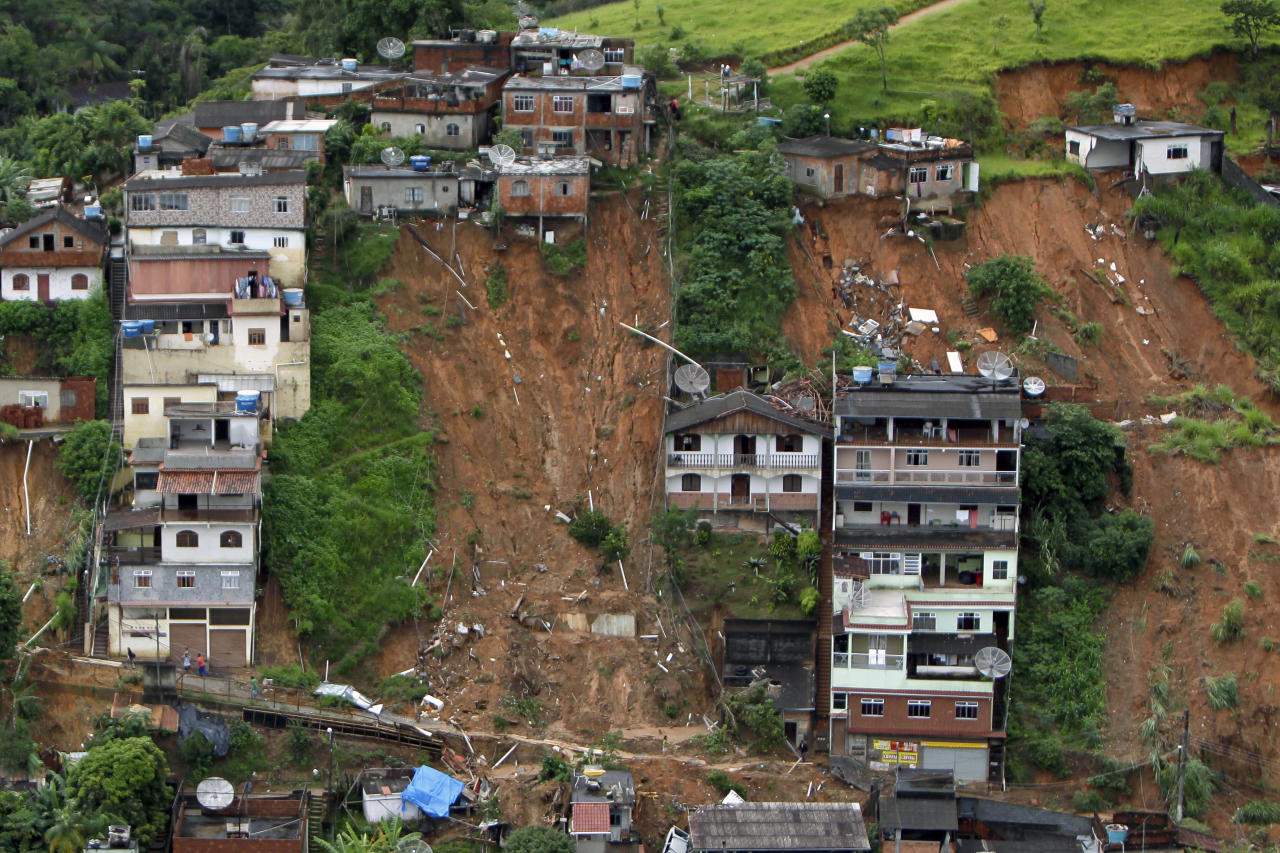 FILE - In this Jan. 16, 2011 file photo, an aerial view shows a neighborhood destroyed by landslides in Nova Friburgo, Brazil. From Chile to Colombia to Mexico, Latin America has been battered recently by wildfires, floods and droughts. While leading climate scientists are unable to pin any single flood or heat wave solely on climate change, experts say the number of extreme weather events is increasing worldwide and the evidence suggests global warming is having an impact. (AP Photo/Felipe Dana, File)