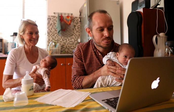 Phillip Lühl holds one of his twin daughters as his mother Frauke looks on while he speaks to his Mexican husband Guillermo Delgado via Zoom meeting in Johannesburg.