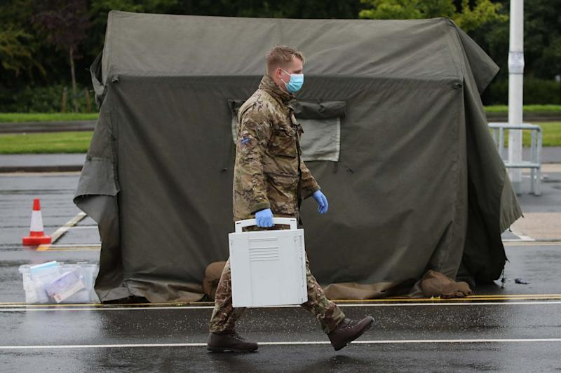 A soldier from the Royal Scots Dragoon Guards carries a container with Covid tests at a mobile testing facility in Stirling (PA)