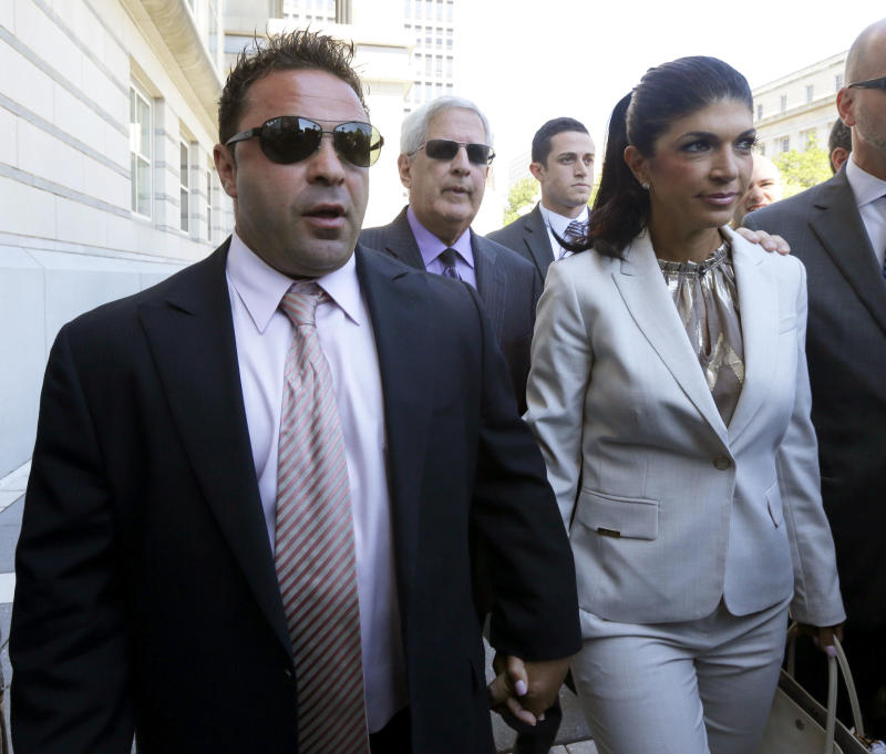 """FILE - In this July 30, 2013 file photo, """"The Real Housewives of New Jersey"""" stars Giuseppe """"Joe"""" Giudice, 43, left, and his wife, Teresa Giudice, 41, of Montville Township, N.J., walk out of Martin Luther King, Jr. Courthouse after an appearance in Newark, N.J. The couple is scheduled to enter a plea before a federal court judge Wednesday afternoon, Aug. 14, 2013. (AP Photo/Julio Cortez, File)"""