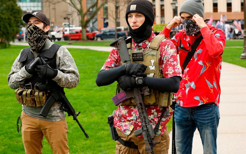 """In this file photo taken on April 30, 2020 Armed protesters provide security as demonstrators take part in an """"American Patriot Rally,"""" organized by Michigan United for Liberty on the steps of the Michigan State Capitol in Lansing, demanding the reopening of businesses. - Jef Kowalsky/AFP/Getty"""