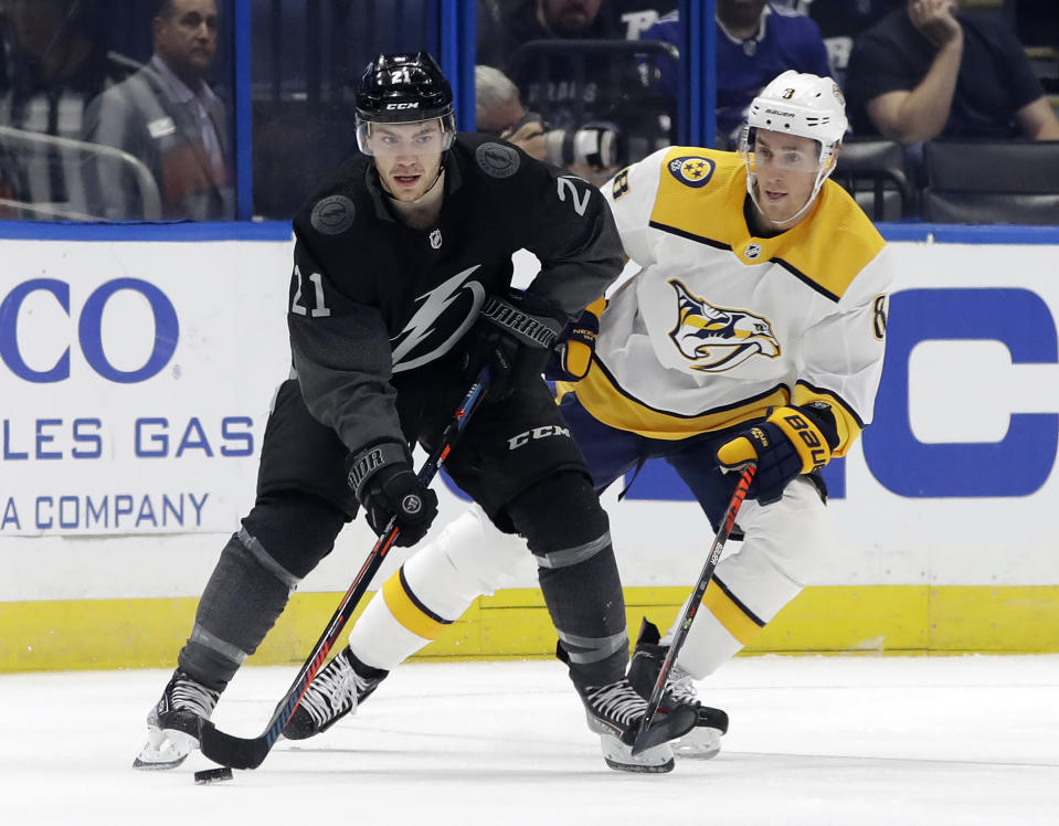 Tampa Bay Lightning center Brayden Point (21) controls the puck in front of Nashville Predators center Kyle Turris (8) during the first period of an NHL hockey game Saturday, Oct. 26, 2019, in Tampa, Fla. (AP Photo/Chris O'Meara)