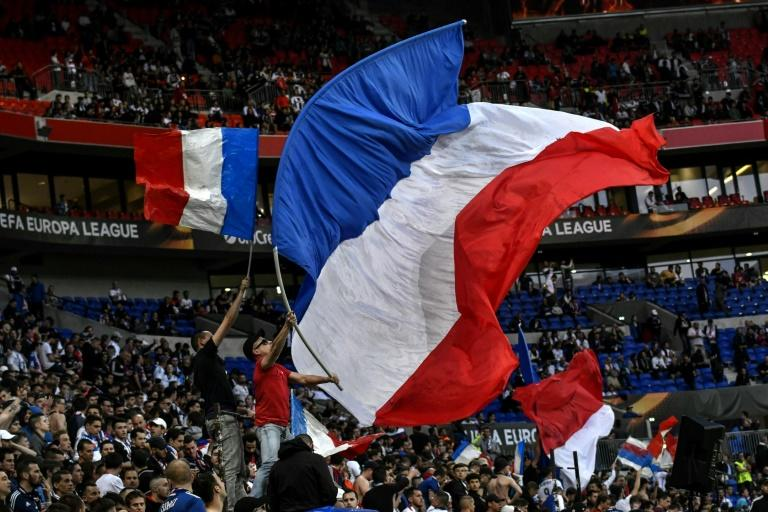 Supporters wave French flags prior to the UEFA Europa League first leg quarter final football match between Lyon (OL) and Besiktas on April 13, 2017, at the Parc Olympique Lyonnais stadium in Decines-Charpieu