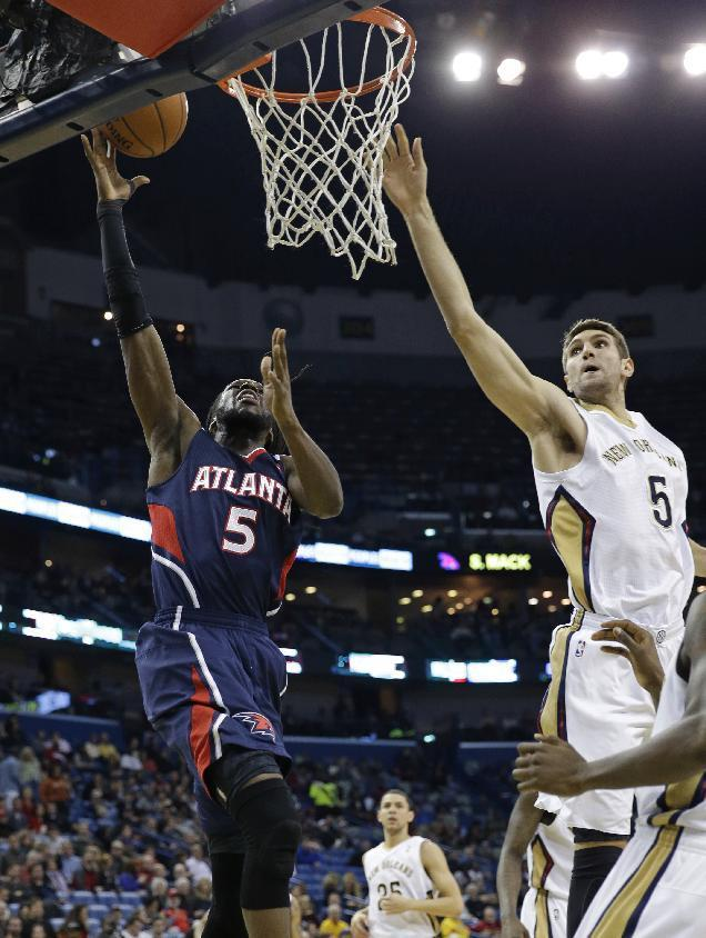 Atlanta Hawks small forward DeMarre Carroll (5) goes to the basket against New Orleans Pelicans center Jeff Withey (5), right, in the first half of an NBA basketball game in New Orleans, Wednesday, Feb. 5, 2014. (AP Photo/Gerald Herbert)