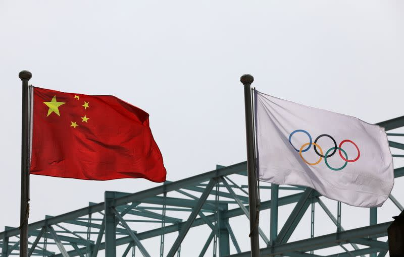 FILE PHOTO: Chinese national flag flutters next to an Olympic flag at the Beijing Organising Committee for the 2022 Olympic and Paralympic Winter Games, in Beijing
