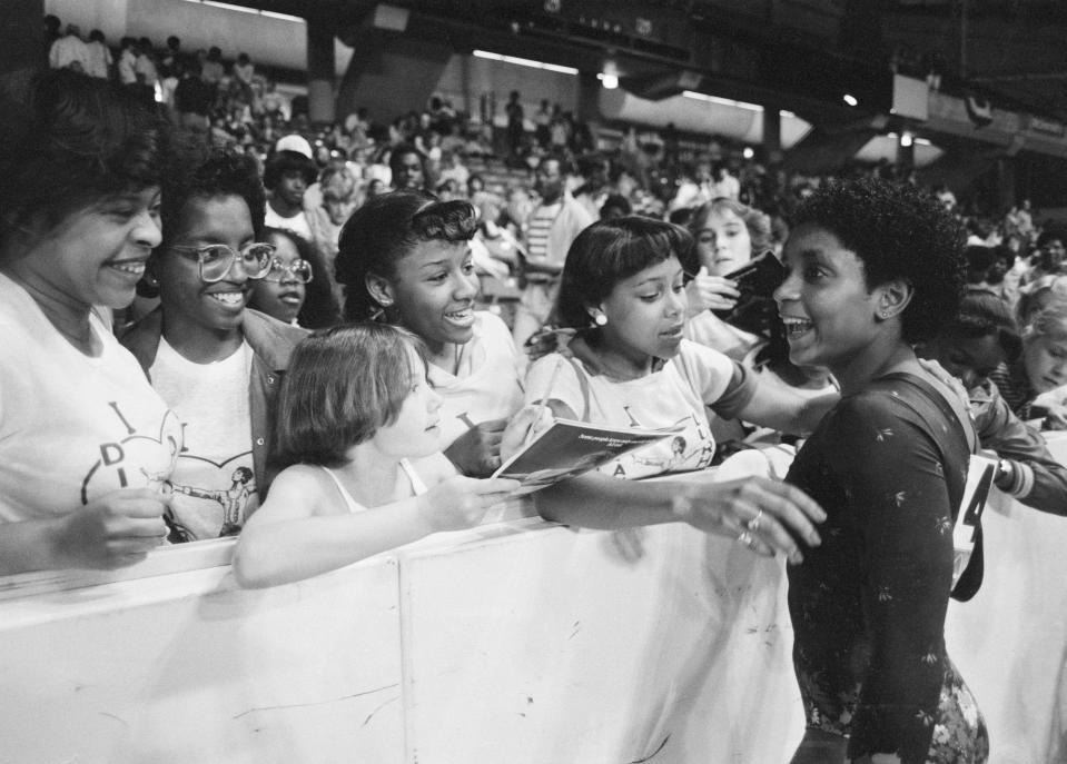 Dianne Durham, 15, of Gary, Ind., right, signs autographs after winning the women's title at the McDonald's U.S.A. Gymnastic Championships at the University of Illinois in Chicago, June 5, 1983. She is the first Black woman to win a major national gymnastics title. (AP Photo/Lisa Genesen)