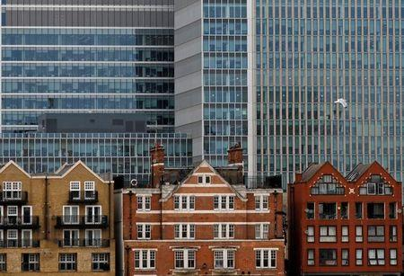 Apartment buildings are backdropped by skyscrapers of banks at Canary Wharf in London
