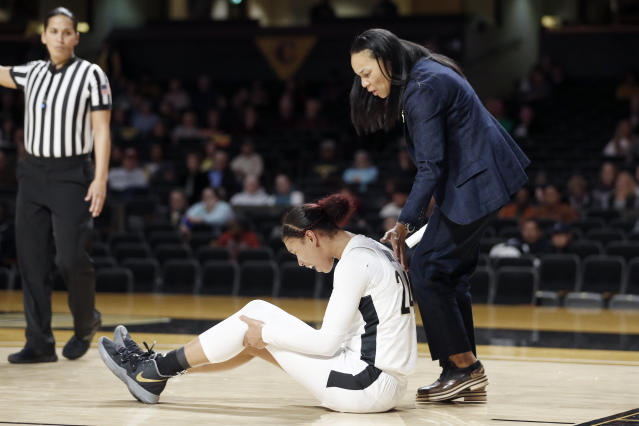 South Carolina head coach Dawn Staley, right, checks on Vanderbilt forward Autumn Newby (24) after Newby was injured during the second half of an NCAA college basketball game Sunday, Jan. 12, 2020, in Nashville, Tenn. South Carolina won 93-57. (AP Photo/Mark Humphrey)
