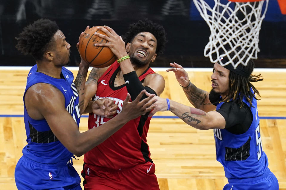 Houston Rockets center Christian Wood, center, attempts a shot against Orlando Magic center Wendell Carter Jr., left, and guard Cole Anthony, right, during the first half of an NBA basketball game, Sunday, April 18, 2021, in Orlando, Fla. (AP Photo/John Raoux)