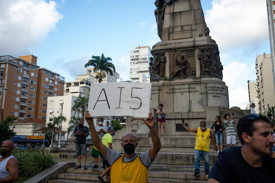 A demonstrator holds up a sign that reads AI-5 that means Institutional Act Number 5 of the military dictatorship period during motorcade to protest against the recommendations for social isolation of the Governor of Sao Paulo, Joao Doria, during the coronavirus disease (COVID-19) outbreak in Santos, Brazil, April 19, 2020. (Photo by Felipe Beltrame/NurPhoto via Getty Images)