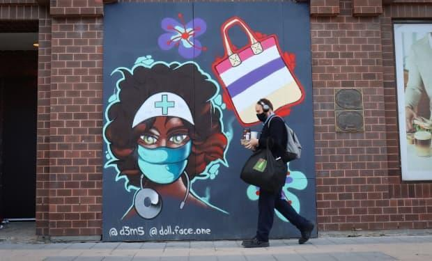 A pedestrian walks past a Rideau Street mural honouring health-care workers on Sept. 16, 2021, during the fourth wave of the COVID-19 pandemic. (Trevor Pritchard/CBC - image credit)