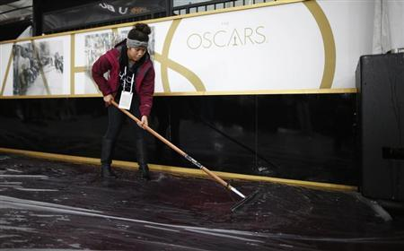 A worker brushes water off red carpet during preparations for 86th Academy Awards in Hollywood
