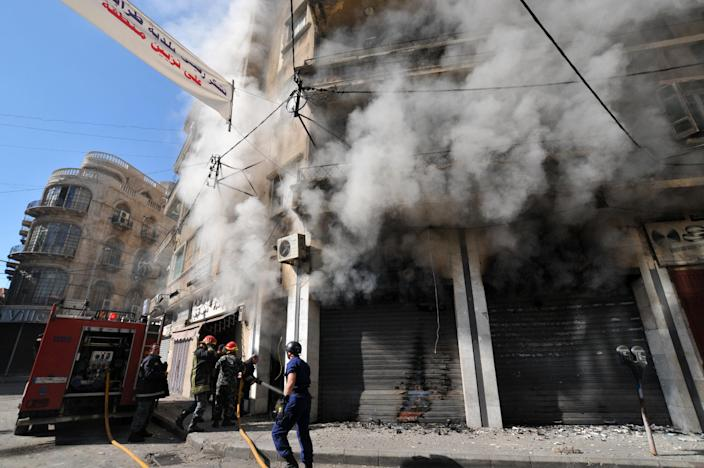 Lebanese firefighters extinguish a flame in a building during clashes between security forces and Islamist gunmen in the historic market of the northern city of Tripoli, on October 25, 2014 (AFP Photo/Ibrahim Chalhoub)