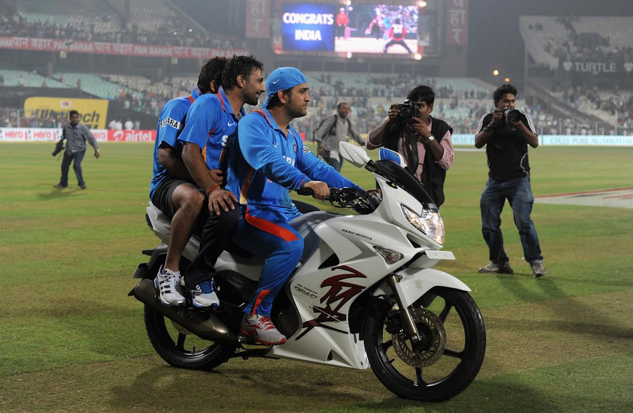 KOLKATA, INDIA - OCTOBER 25:  MS Dhoni and Praveen Kumar of India celebrate by doing a lap of honour on the man of the series's motorbike after the 5th One Day International between India and England, at Eden Gardens on October 25, 2011 in Kolkata, India.  (Photo by Gareth Copley/Getty Images)