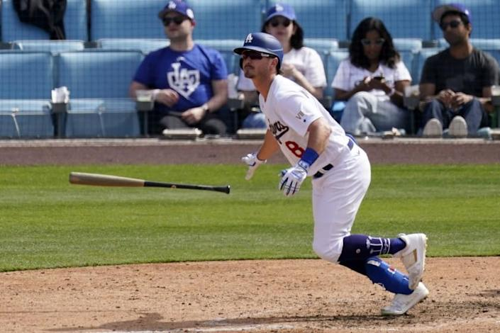 Los Angeles Dodgers' Zach McKinstry, right, runs to first after hitting a two-run home run during the seventh inning.