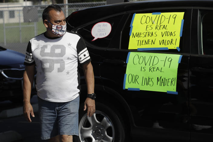 Disney employee Manuel Ortiz tapes signs on is car during a protest to demand a safe reopening amid the coronavirus pandemic Saturday, June 27, 2020, in Anaheim, Calif. Workers are demanding regular testing, stricter cleaning protocols and higher staffing levels. Disney had originally proposed reopening on July 17th but announced this week it was postponing. (AP Photo/Marcio Jose Sanchez)