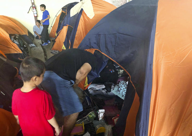 """Julio Lopez, a Salvadoran man who wants to seek asylum in the United States with his family, speaks with his wife inside their tent at a migrant shelter in Tijuana with his 5-year-old son by his side in Tijuana, Mexico, Thursday, Sept. 26, 2019. He asked that their faces not be shown. The Trump administration played """"bait and switch"""" by instructing migrants to wait in Mexico for an opportunity to apply for asylum before imposing sharp restrictions on eligibility, attorneys said in a court filing Thursday. (AP Photo/Elliot Spagat)"""