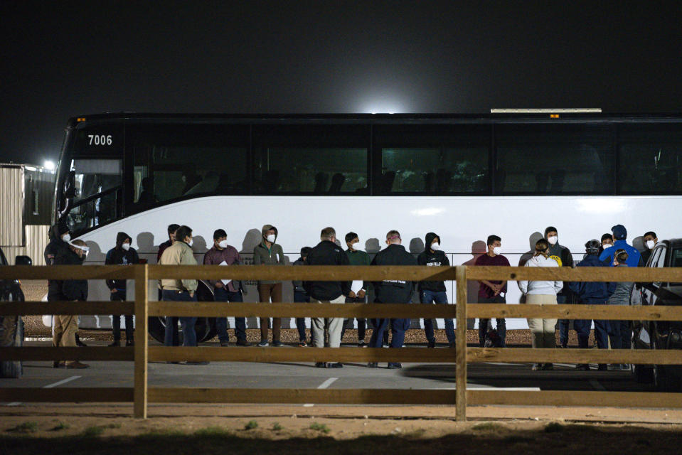 FILE - In this March 14, 2021, file photo, migrant children and teenagers are processed after entering the site of a temporary holding facility south of Midland, Texas. Migration flows to the U.S. from Mexico are surging for the third time in seven years under Republican and Democratic presidents — and for similar reasons. (Eli Hartman/Odessa American via AP, File)