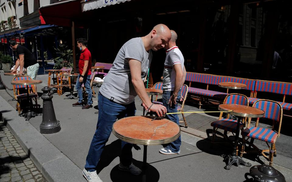 Waiters prepare tables on the terrace at a Parisian cafe, with each table placed apart in accordance with social distancing guidelines - Christophe Ena/AP