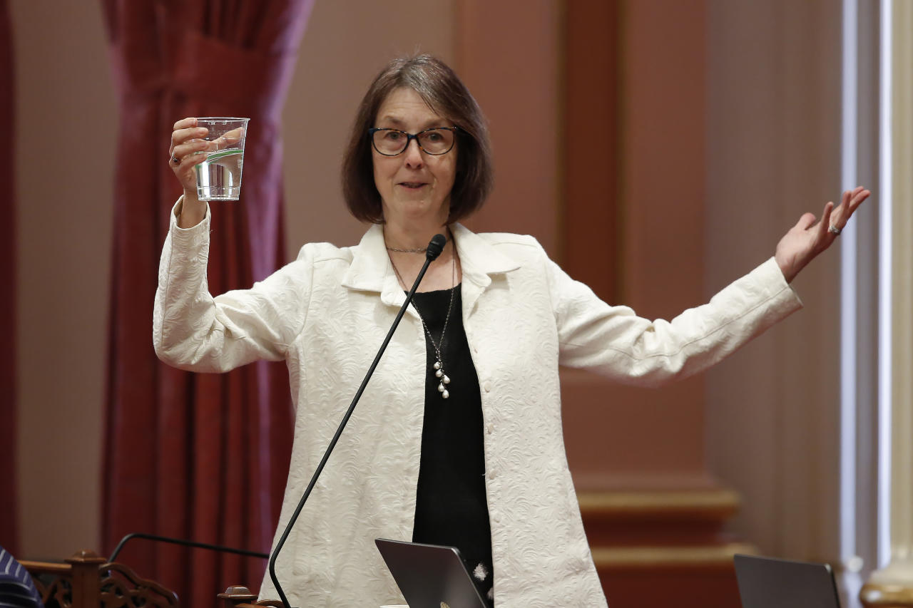 State Sen. Nancy Skinner, D-Berkeley holds up a glass of water as she describes the state budget plan in the optimistically as being half-full, as lawmakers debated the 2019-2020 spending plan in Sacramento, Calif., Thursday, June 13, 2019. Both houses of the Legislature approved the $214.8 billion state budget that spends more on health care and education, bolsters the state's top firefighting agency and boost state reserves.(AP Photo/Rich Pedroncelli)