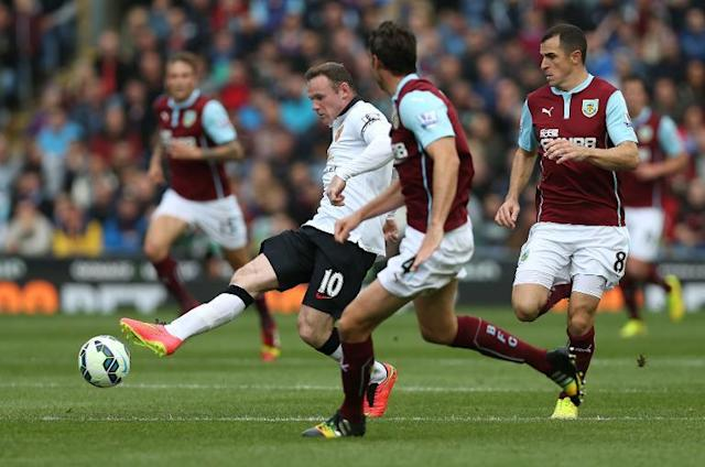 """Manchester United's English striker Wayne Rooney (L) passes the ball around Burnley's Northern Irish defender Michael Duff (C) and English midfielder Dean Marney (R) during the English Premier League football match on August 30, 2014 RESTRICTED TO EDITORIAL USE. No use with unauthorized audio, video, data, fixture lists, club/league logos or """"live"""" services. Online in-match use limited to 45 images, no video emulation. No use in betting, games or single club/league/player publications (AFP Photo/Ian MacNicol)"""