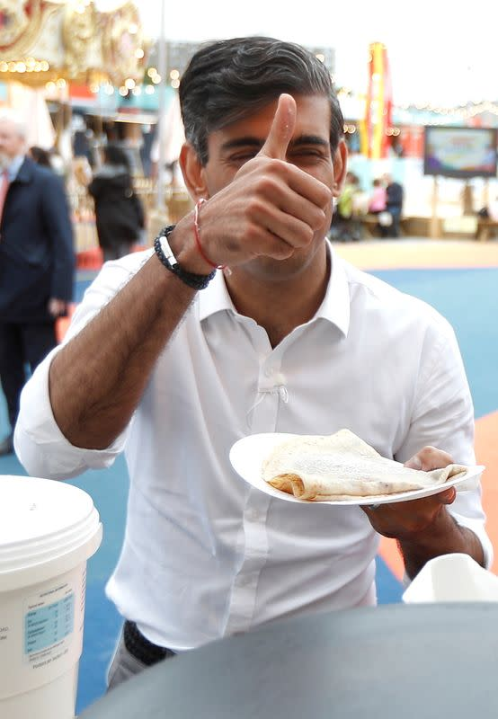 FILE PHOTO: Britain's Chancellor Rishi Sunak gestures as he takes a pancake from a stall at the London Wonderground comedy and music festival venue in London