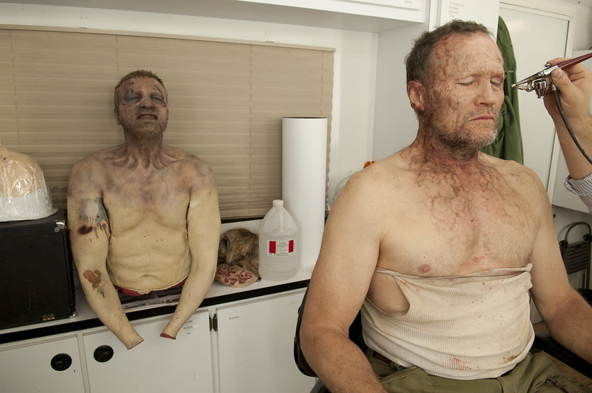 <p>As Michael Rooker gets zombified for Merle Dixon's big death, a zombie Merle dummy sits behind him, just waiting to be stabbed by Merle's brother, Daryl.<br /><br />(Photo: AMC) </p>