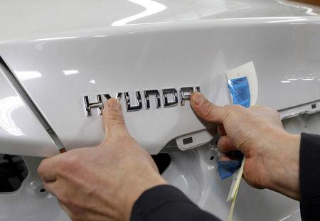 A worker fixes the Hyundai logo on a vehicle at a plant of Hyundai Motor in Asan, south of Seoul, February 9, 2012.  REUTERS/Lee Jae-Won/File Photo