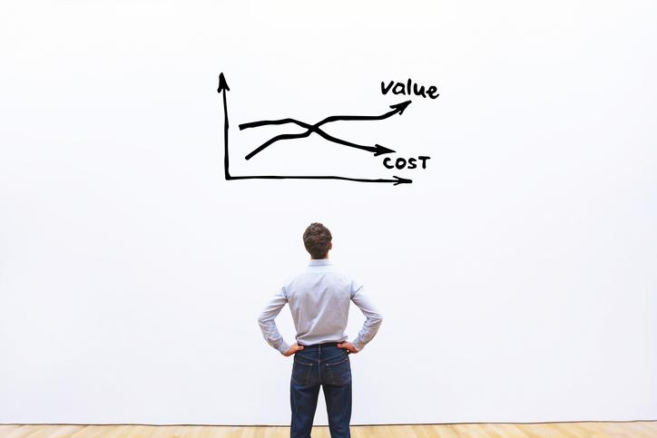 A man staring at a chart of expenses and profits. The chart has two intersecting lines, one labeled value and the other labeled cost.