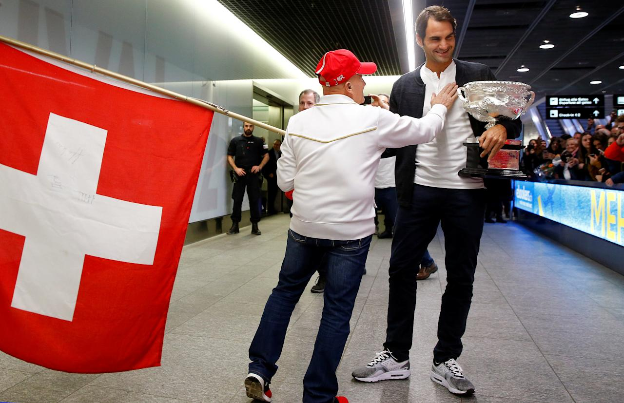 Switzerland's Roger Federer holds his Australian Open trophy as he is welcomed by a fan upon his arrival at Zurich airport January 31, 2017.  REUTERS/Arnd Wiegmann     TPX IMAGES OF THE DAY