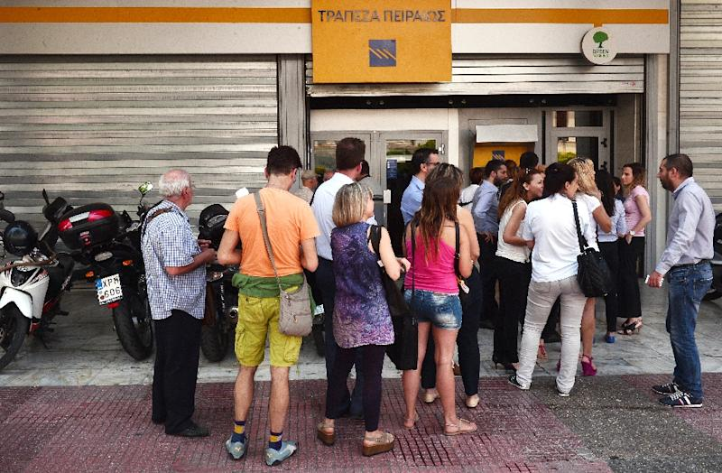 People queue at the ATM machines of the Piraeus bank in central Athens. The country's main banks took a heavy blow, with National Bank and Piraeus falling to the maximum allowed level of minus 30 percent (AFP Photo/Louisa Gouliamaki)