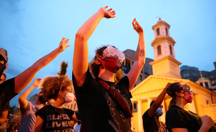Protestors stand with their hands up on Black Lives Matter Plaza in front of St. John's Episcopal Church after police clashed with demonstrators trying to pull down the statue of U.S. President Andrew Jackson in Lafayette Park across from the White House during racial inequality protests in Washington, U.S., June 22, 2020. (Tom Brenner/Reuters)
