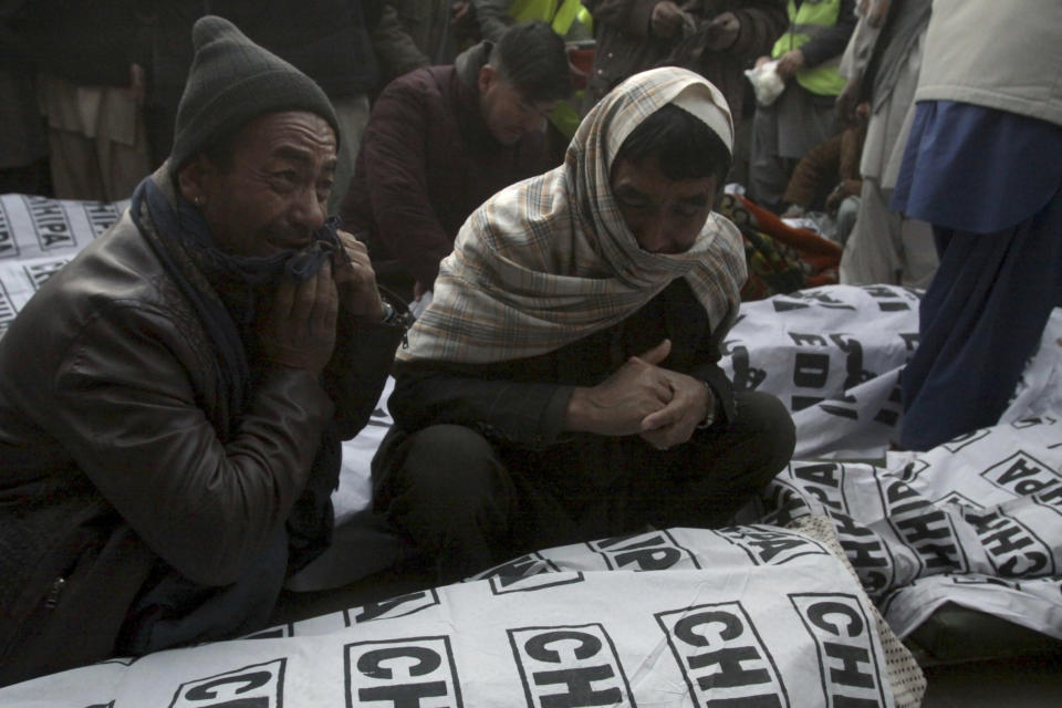 People from the Shiite Hazara community mourn around the bodies of coal mine workers who were killed by unknown gunmen near the Machh coal field, in Quetta, Pakistan, Sunday, Jan. 3, 2021. Gunmen opened fire on a group of minority Shiite Hazara coal miners after abducting them, killing 11 in southwestern Baluchistan province early Sunday, a Pakistani official said. (AP Photo/Arshad Butt)