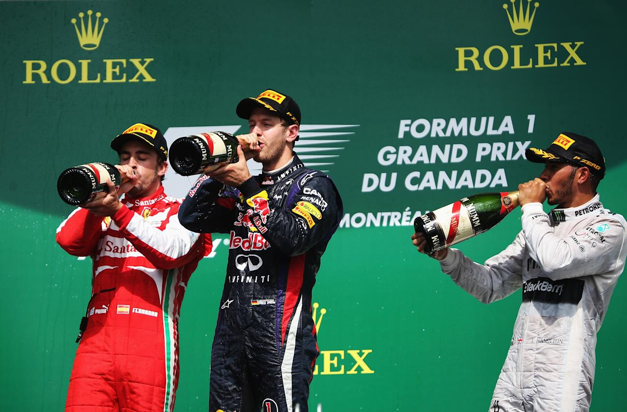 MONTREAL, QC - JUNE 09: Sebastian Vettel (centre) of Germany and Infiniti Red Bull Racing celebrates with second placed Fernando Alonso (left) of Spain and Ferrari and third placed Lewis Hamilton (right) of Great Britain and Mercedes GP following the Canadian Formula One Grand Prix at the Circuit Gilles Villeneuve on June 9, 2013 in Montreal, Canada. (Photo by Mark Thompson/Getty Images)