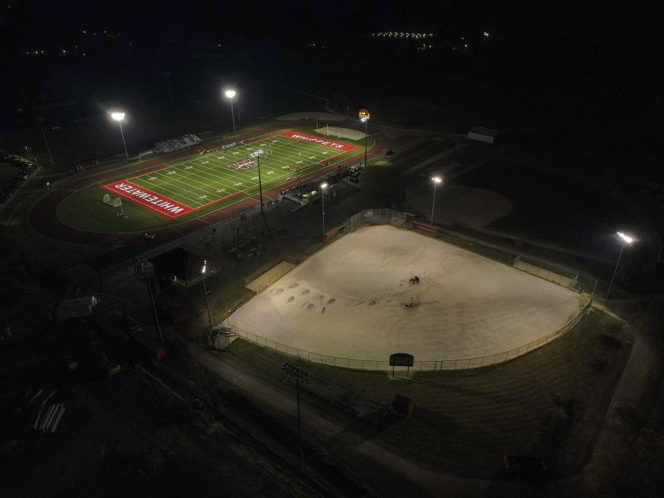 A football field, top, and baseball field under construction are lit up at Whitewater High School Friday, Oct. 1, 2021, in Whitewater, Wis. A growing number of school districts in the U.S. are using federal pandemic funding on athletics projects. When school officials at Whitewater learned they would be getting $2 million in pandemic relief this year, they decided to set most of it aside to cover costs from their current budget, freeing up $1.6 million in local funding that's being used to build new synthetic turf fields for football, baseball and softball. (AP Photo/Morry Gash)