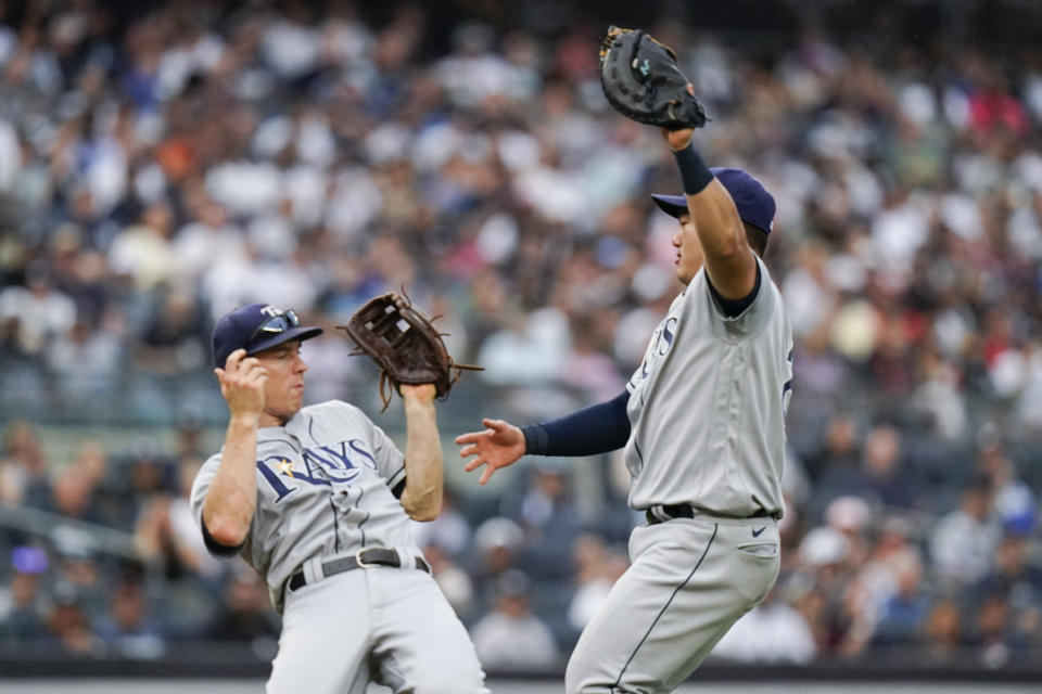 Tampa Bay Rays first baseman Ji-Man Choi, of Korea, right, and third baseman Joey Wendle collide as Choi caught a pop fly by New York Yankees' Giancarlo Stanton for an out during the seventh inning of a baseball game Sunday, Oct. 3, 2021, in New York. (AP Photo/Frank Franklin II)