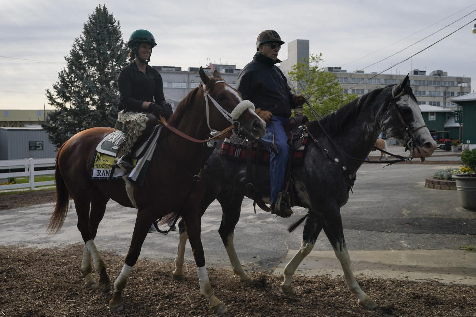 Exercise rider Jade Cunningham, left, walks with Preakness entrant Ram and trainer D. Wayne Lukas after a training session ahead of the Preakness Stakes horse race at Pimlico Race Course, Wednesday, May 12, 2021, in Baltimore. (AP Photo/Julio Cortez)