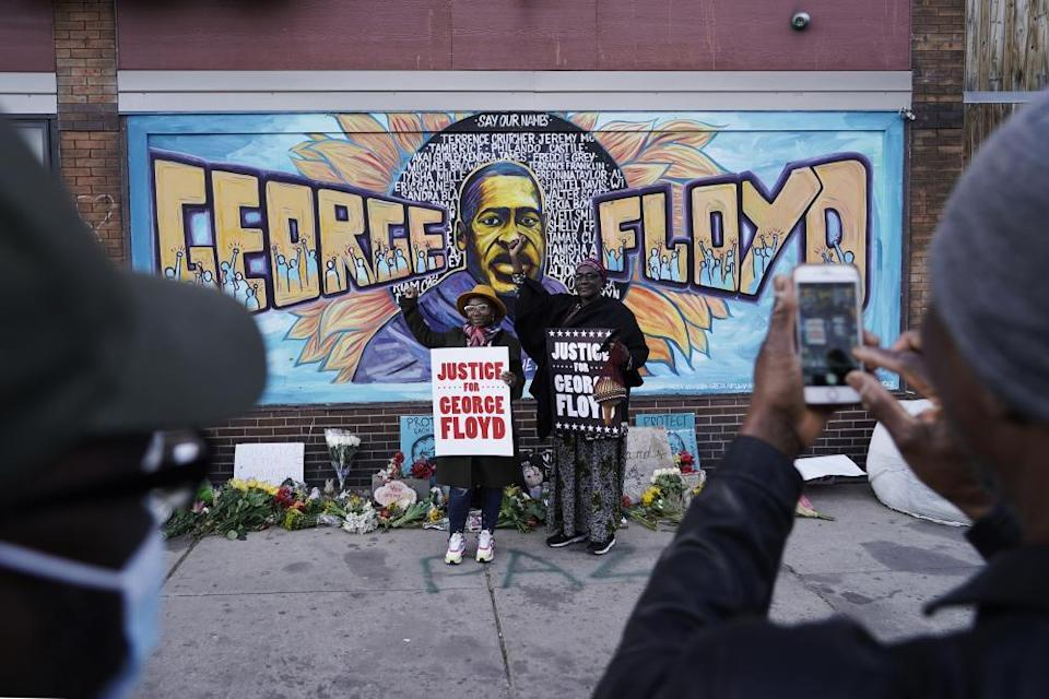 People pose for pictures in front of a mural for George Floyd in Minneapolis.