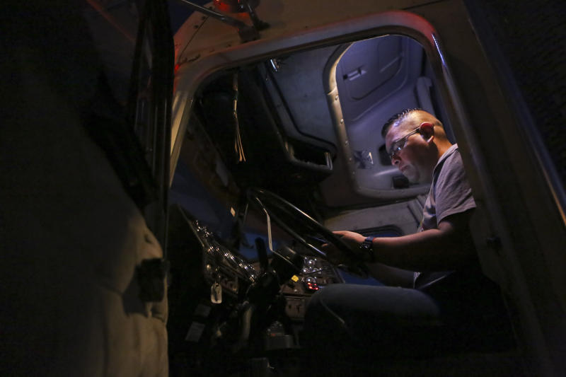 A truck driver uses his cell phone while he waits to cross the border with the U.S. in Ciudad Juarez, Mexico, Tuesday, April 9, 2019. The Trump administration has reassigned so many inspectors from U.S.-Mexico border crossings that it has caused huge traffic backups for truckers who are waiting in line for hours and in some case days to get shipments to the U.S. (AP Photo/Christian Torres)