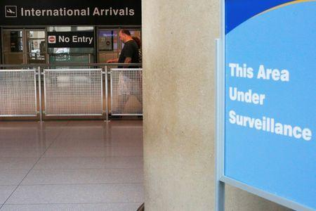 A sign warns of surveillance at the International Arrival area at Logan Airport