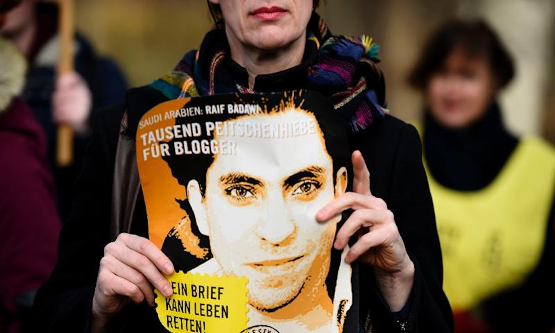 An Amnesty International activist holds a picture of Saudi blogger Raif Badawi during a protest against his flogging punishment on January 29, 2015 in front of Saudi Arabia's embassy to Germany in Berlin. The 30-year-old Saudi has been sentenced to 1,000 lashes for insulting Islam and is serving a 10-year jail term - a case which has drawn widespread international criticism. AFP PHOTO / TOBIAS SCHWARZ (AFP Photo/Tobias Schwarz)