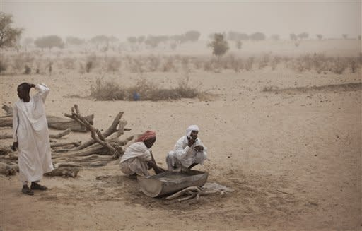 Hissaeni Abdoulaye, 46, center, washes his face with water from an animal trough, after using a donkey to pull it up from a well which took twenty men a week to dig by hand, in a wadi near Tchyllah, a desert village in the Sahel belt of Chad, Thursday, April 19, 2012. UNICEF estimates that 127,000 children under 5 in Chad's Sahel belt will require lifesaving treatment for severe acute malnutrition this year, with an estimated 1 million expected throughout the wider Sahel region of West and Central Africa in the countries of Niger, Nigeria, Mali, Chad, Burkina Faso, Cameroon, Senegal and Mauritania. The organization says the current food and nutrition crisis stems from scarce rainfalls in 2011, which caused poor harvests and livestock production, though the situation in Chad has also been exacerbated by an influx of Chadians returning from Libya as a result of the conflict there. (AP Photo/Ben Curtis)
